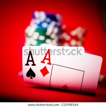 Stack of chips and two aces on a poker table