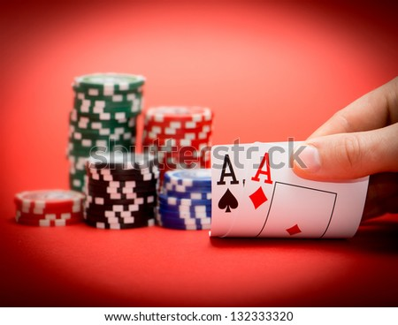 Stack of chips and two aces on a red poker table - stock photo