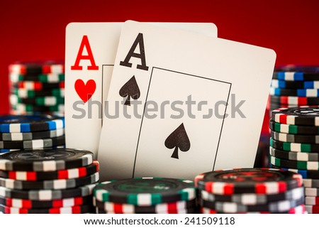 Stack of chips and two aces on the table on the red baize - poker game concept - stock photo