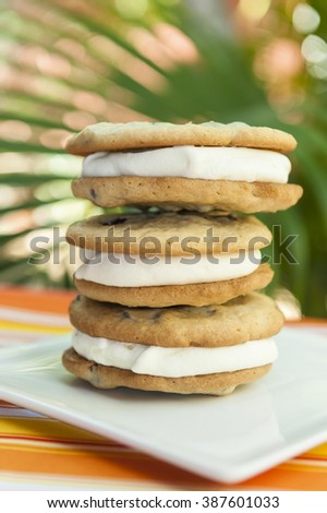 Stack of chocolate chip cookie and vanilla ice cream sandwiches with a tropical background