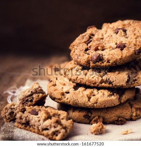 Stack of Chocolate chip cookies on wooden background. Stacked chocolate chip cookies shot with selective focus. - stock photo