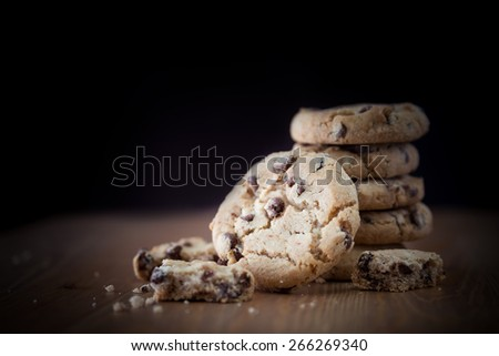 Stack of chocolate chip cookies on wooden table. Shallow DOF and lightly toned. Focus on the front cookie - stock photo