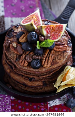 Stack of chocolate pancakes decorated with berries - stock photo