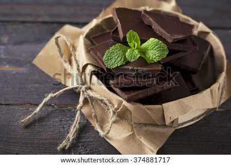 Stack of chocolate slices with mint leaf on a dark wooden background.Selective focus.