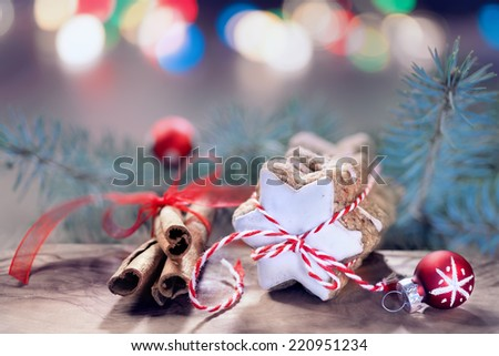 Stack of Christmas star-shaped cookies tied up with red-white twisted cord, cinnamon sticks on abstract Christmas background. Shallow DOF, focus on the knot. Toned image, space for your text. - stock photo