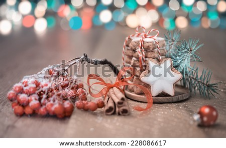 Stack of Christmas star-shaped cookies tied up with red-white twisted cord, cinnamon sticks on abstract Christmas background. Shallow DOF, focus on the knot. Toned image