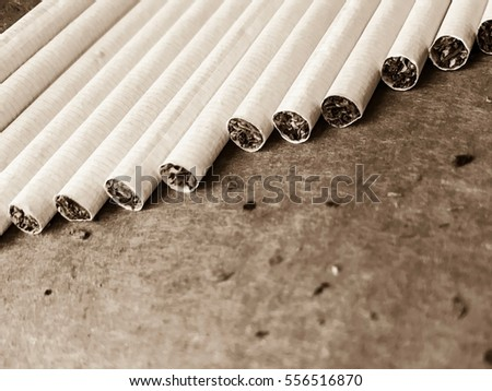 Stack of cigarettes in the line on a rough background sepia old vintage photo wallpaper