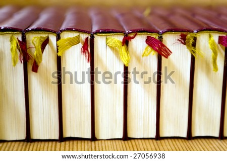 stack of classic leather bound books with colourful fabric bookmarks - stock photo