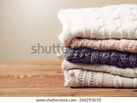 stack of clothes from knitted knitwear on a wooden background, toned image - stock photo
