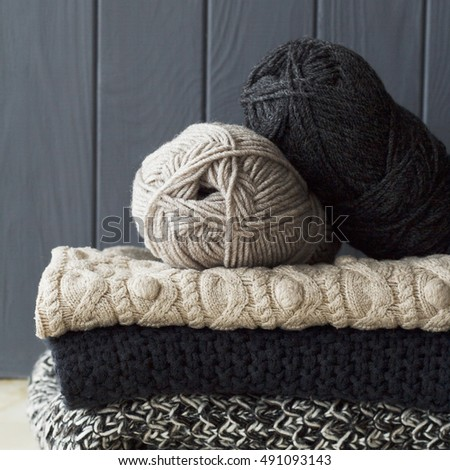 Stack of clothes from knitted knitwear over grey wooden background