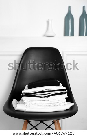 Stack of clothes on black chair over white wall background