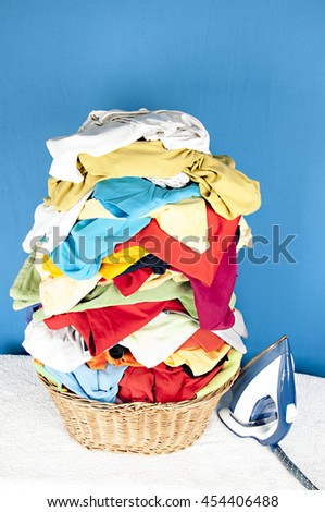 stack of clothes prepared to ironing with iron - stock photo