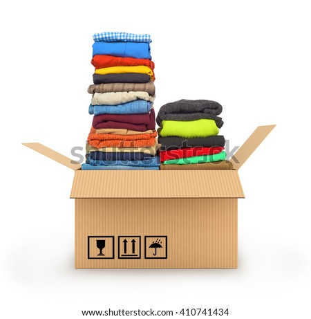 Stack of clothing in cardboard box isolated on white, delivery of garments concept - stock photo