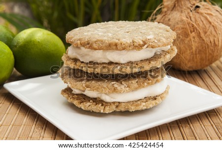 Stack of coconut lime ice cream sandwiches with limes and a coconut