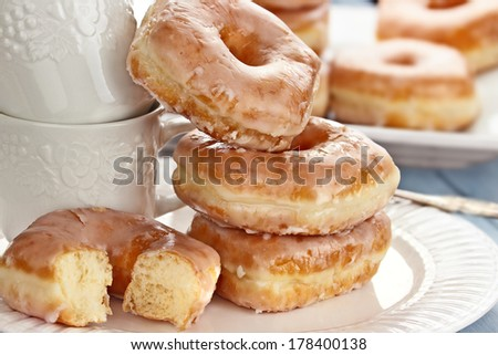 Stack of coffee cups and delicious glazed donuts. - stock photo
