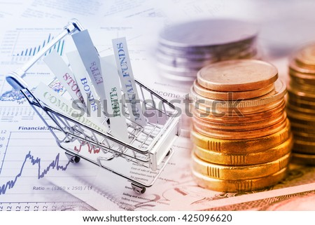 Stack of coins and a trolley with various types of financial investment products i.e. stocks, commodities, bonds, REITs, mutual funds, ETFs. Wealth management with risk diversification concept. - stock photo