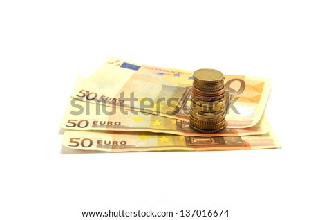Stack of coins and banknotes on a white background - stock photo