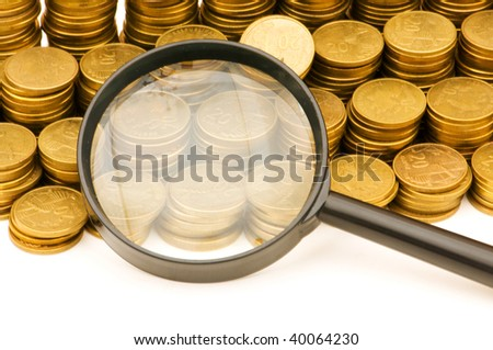 Stack of coins and magnifying glass on the white