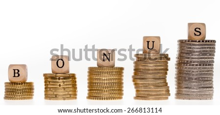 Stack of coins and wood dice with the word bonus / Bonus