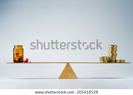 Stack of coins balancing on seesaw over a bottle of pills - stock photo