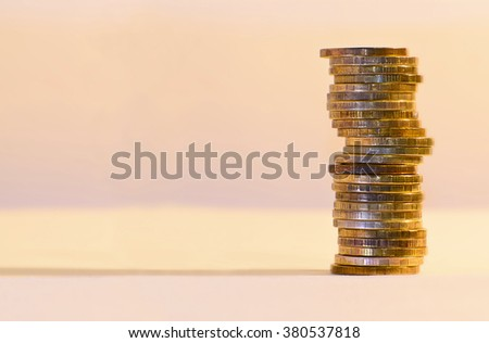 Stack of coins close-up on a gold background. - stock photo