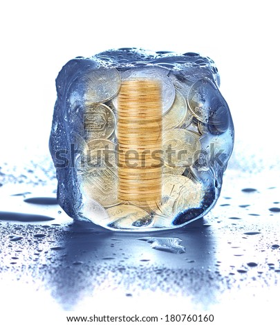 Stack of coins in the ice cube. frozen accounts - stock photo