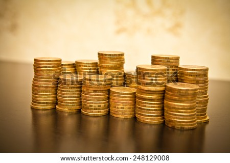stack of coins on a black wooden background, shallow depth of field