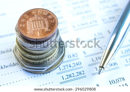 Stack of Coins with pen and financial statement background - stock photo