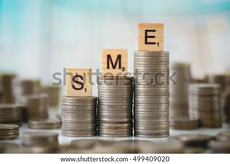 Stack of Coins with Wooden Letters