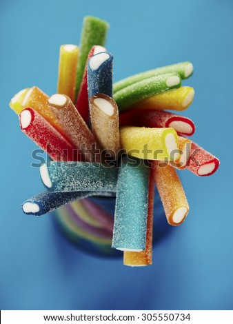 Stack of colored gummy sweet sticks on blue background - stock photo