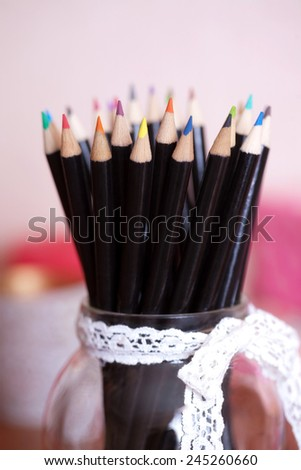 Stack of colored pencils in a glass - stock photo