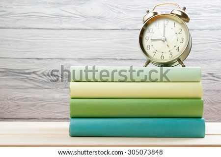 Stack of colorful books and alarm clock on wooden table. Back to school. Copy space - stock photo