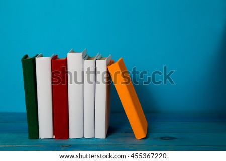 Stack of colorful books, grungy blue background, free copy space. Vintage old hardback books on wooden shelf, deck table, no labels, blank spine. Back to school - stock photo