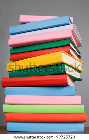 Stack of colorful books on a gray background