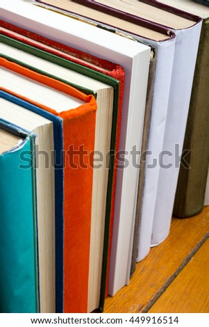 Stack of colorful books on vintage old hardback books on wooden shelf on the deck table, no labels, blank spine. Back to school. Education background with free copy space - stock photo