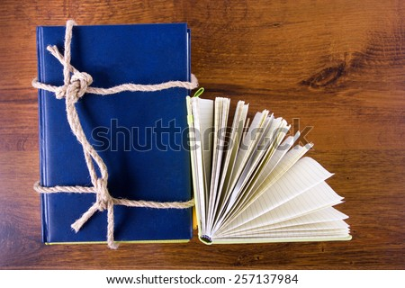Stack of colorful books tied with a rope on wooden background. Back to school.  - stock photo