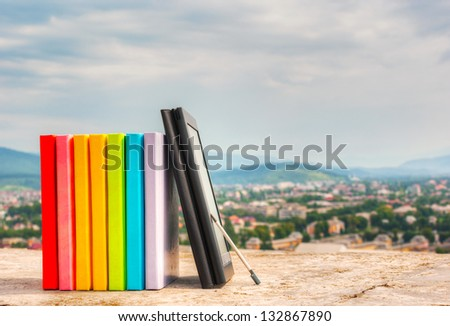 Stack of colorful books with electronic book reader - stock photo