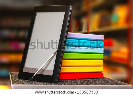 Stack of colorful books with electronic book reader at a book store - stock photo