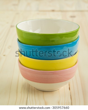 Stack of Colorful Bowls on Wooden Background - stock photo