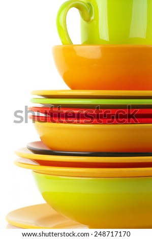Stack of colorful ceramic dishware close-up on white background. - stock photo