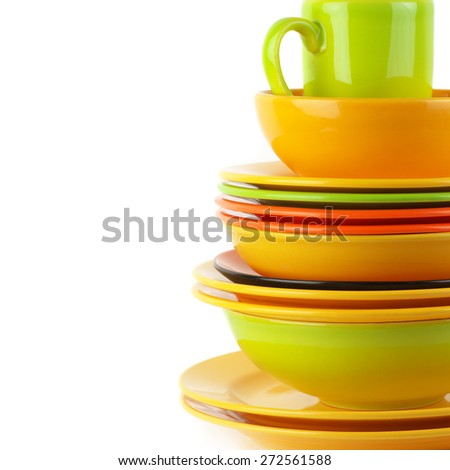 Stack of colorful ceramic dishware close-up on white background with copy space. - stock photo