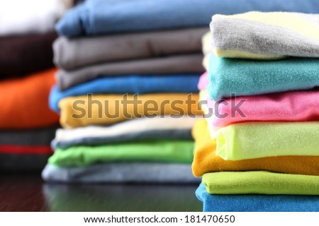 Stack of colorful clothes, on dark background - stock photo