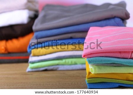 Stack of colorful clothes, on light background - stock photo