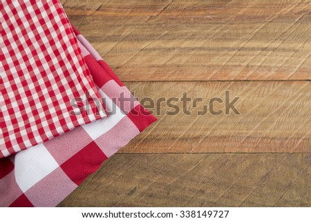Stack of colorful dish towels on wooden table.