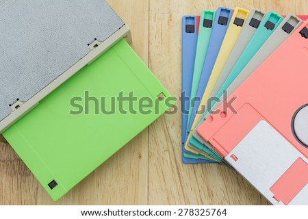 Stack of colorful floppy disks and a floppy disk drive on a wooden table - stock photo