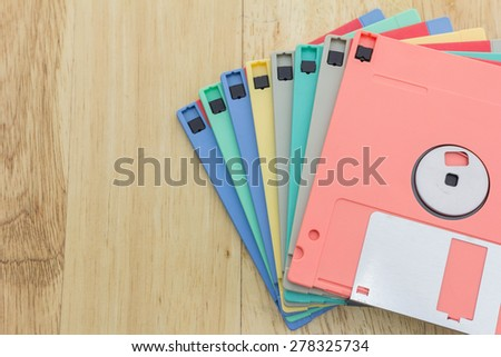 Stack of colorful floppy disks on a wooden table - stock photo