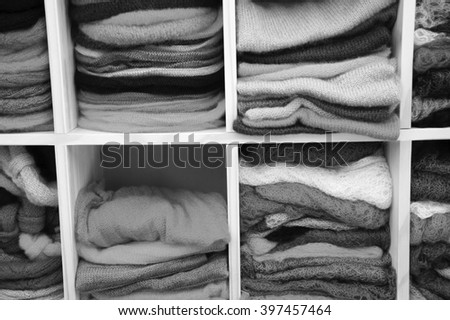 Stack of colorful  knitted colorful clothes - sweaters, dresses, cardigans etc. Aged photo. Black and white.
