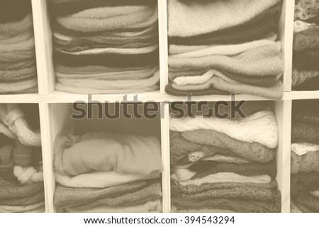 Stack of colorful  knitted colorful clothes - sweaters, dresses, cardigans etc. Aged photo with haze effect. Sepia. - stock photo