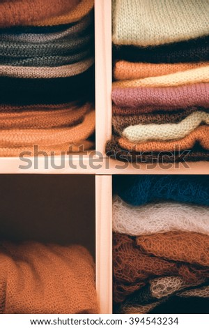 Stack of colorful  knitted colorful clothes - sweaters, dresses, cardigans etc.  Toned photo. - stock photo