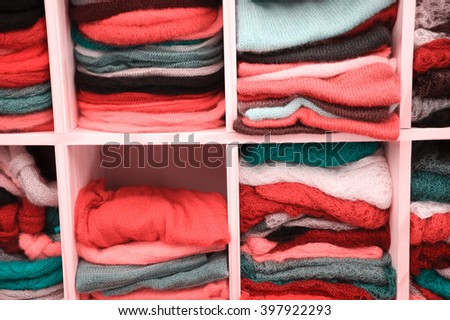 Stack of colorful  knitted colorful clothes - sweaters, dresses, cardigans etc. Toned photo.